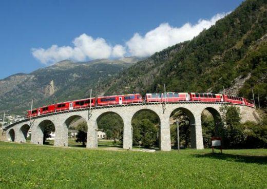 Rhaetische Bahn/RhB – Der Bernina Express auf dem bekannten Kreisviadukt bei Brusio. Eine Fahrt von den Gletschern zu den Palmen. Quelle: Rhätische Bahn/G. Murbach