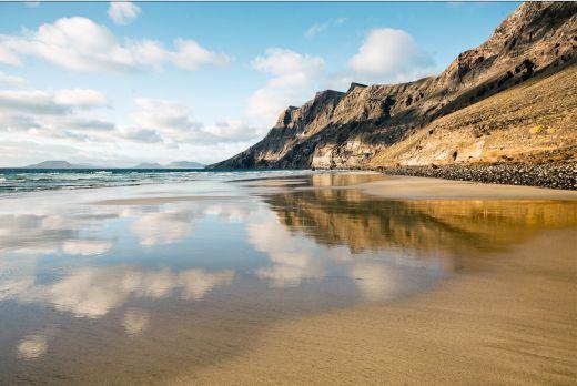 Der kilometerlange feine Sandstrand von Famara bietet ausreichend Platz für Erkundungstouren durch weitgehend unberührte Natur. Bildnachweis: Turismo Lanzarote
